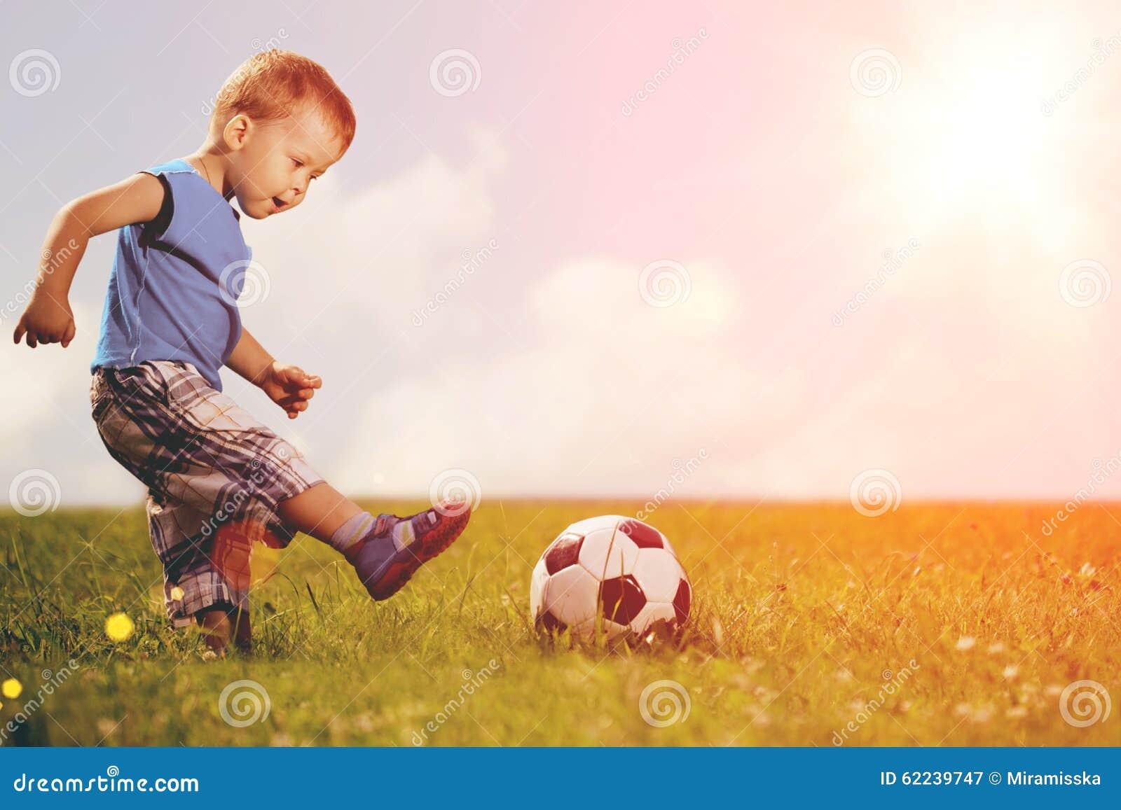 Niño de los deportes Muchacho que juega al balompié Bebé con la bola en campo de deportes