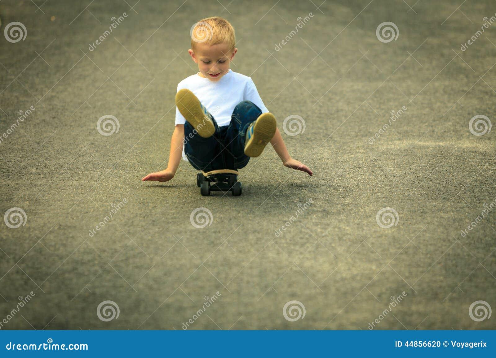 Niño del muchacho del patinador con su monopatín Actividad al aire libre