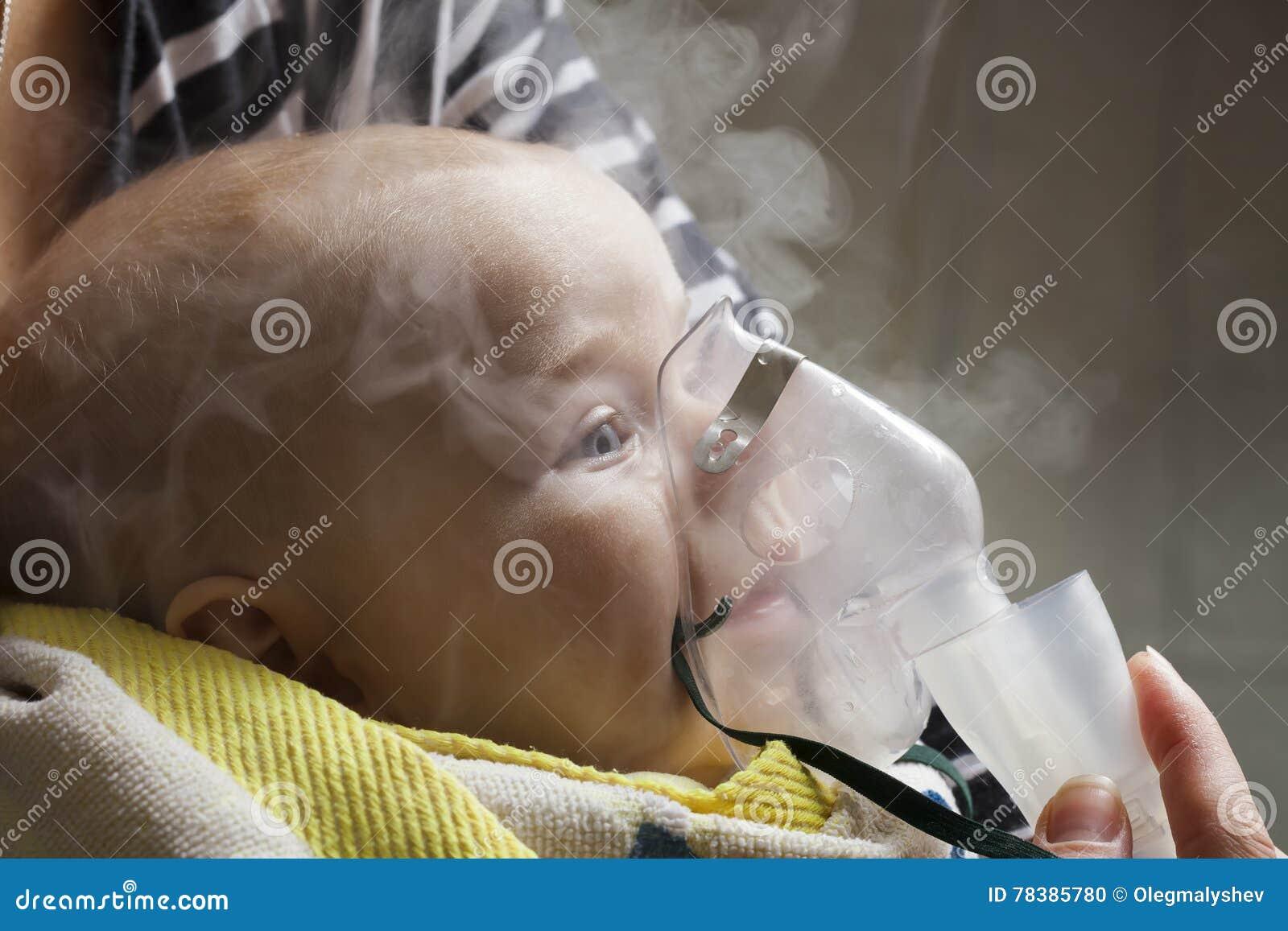 Niño del niño de la inhalación de la mamá bajo un año