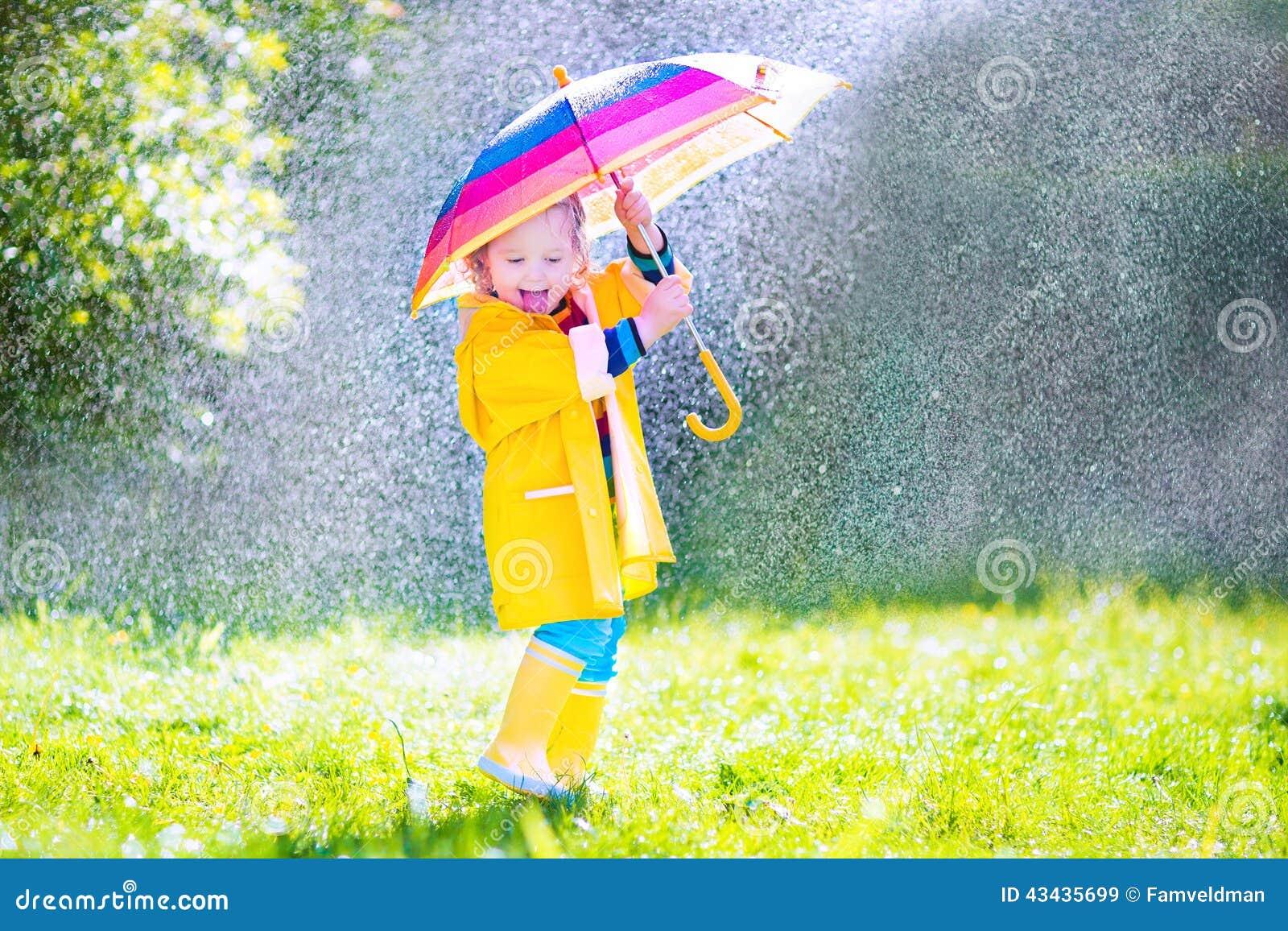 Niño divertido con el paraguas que juega en la lluvia