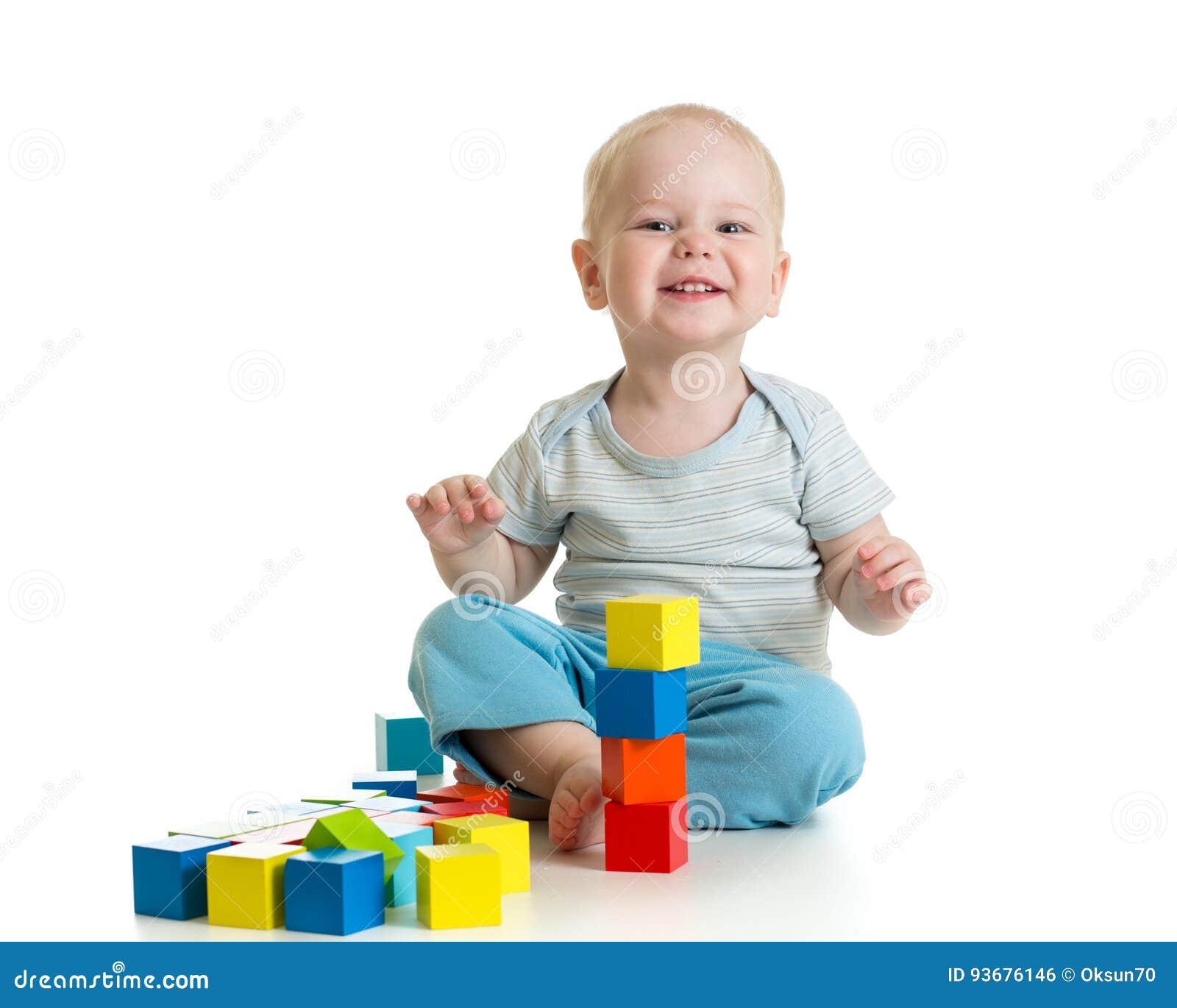 Niño divertido que juega los bloques de madera del juguete aislados en blanco