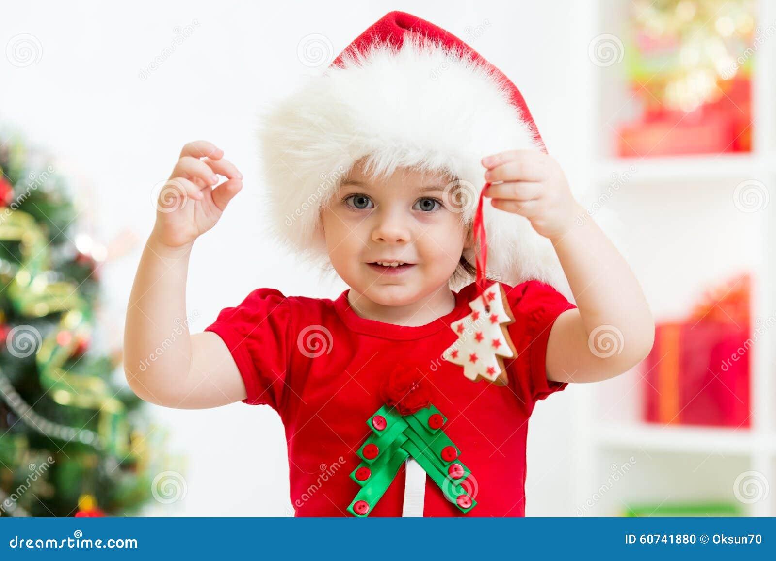 Embrome a la muchacha en el sombrero de Papá Noel que sostiene las galletas  de la Navidad b8e51961041