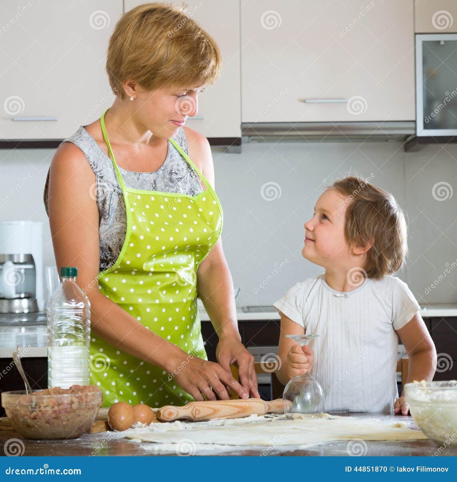 Niño feliz con la mujer que hace las bolas de masa hervida de la carne