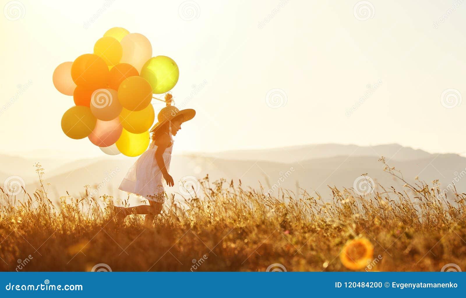 Niño feliz con los globos en la puesta del sol en verano