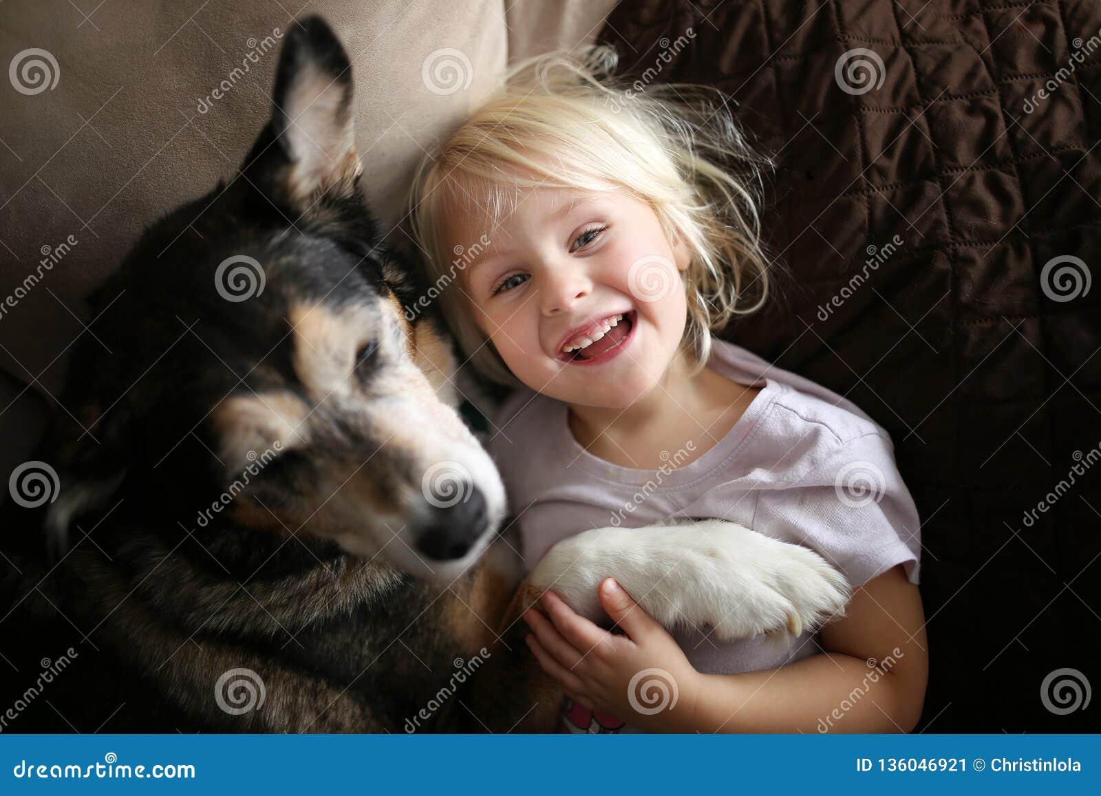 Niño feliz, de risa de la niña que abraza el perro casero en el sofá