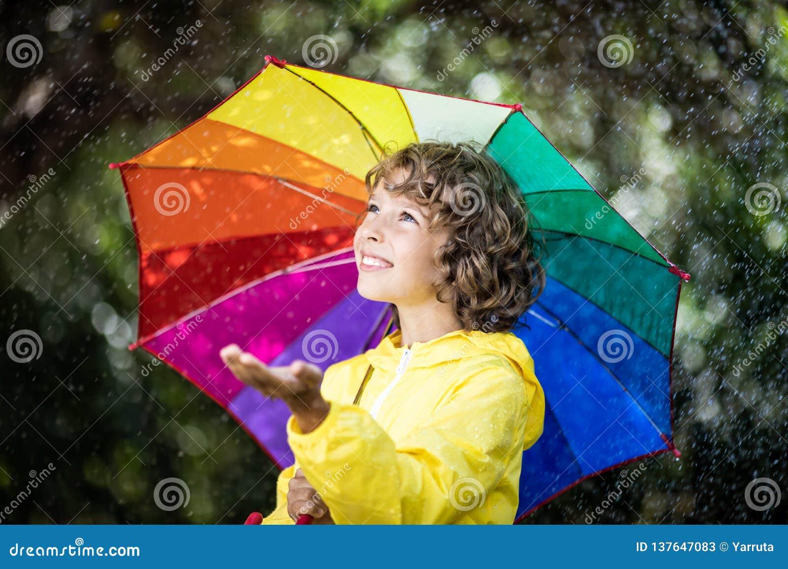 Niño feliz que juega bajo la lluvia