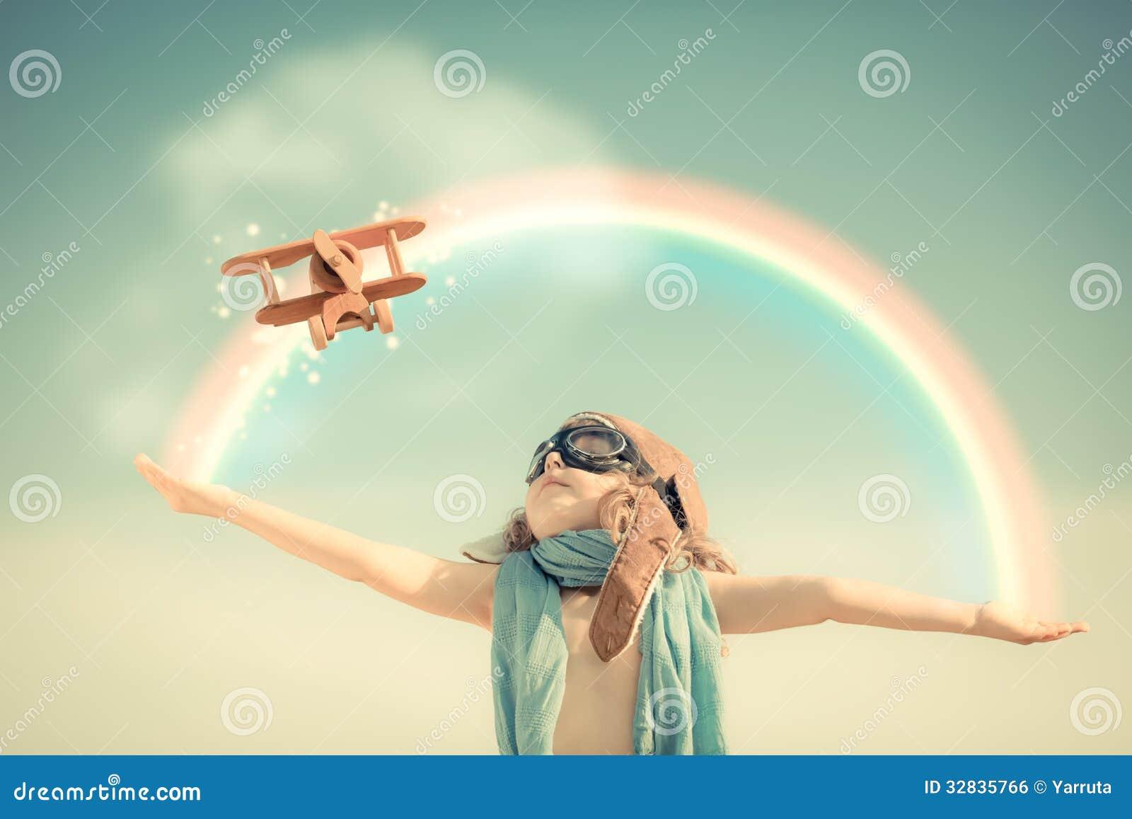 Niño feliz que juega con el aeroplano del juguete