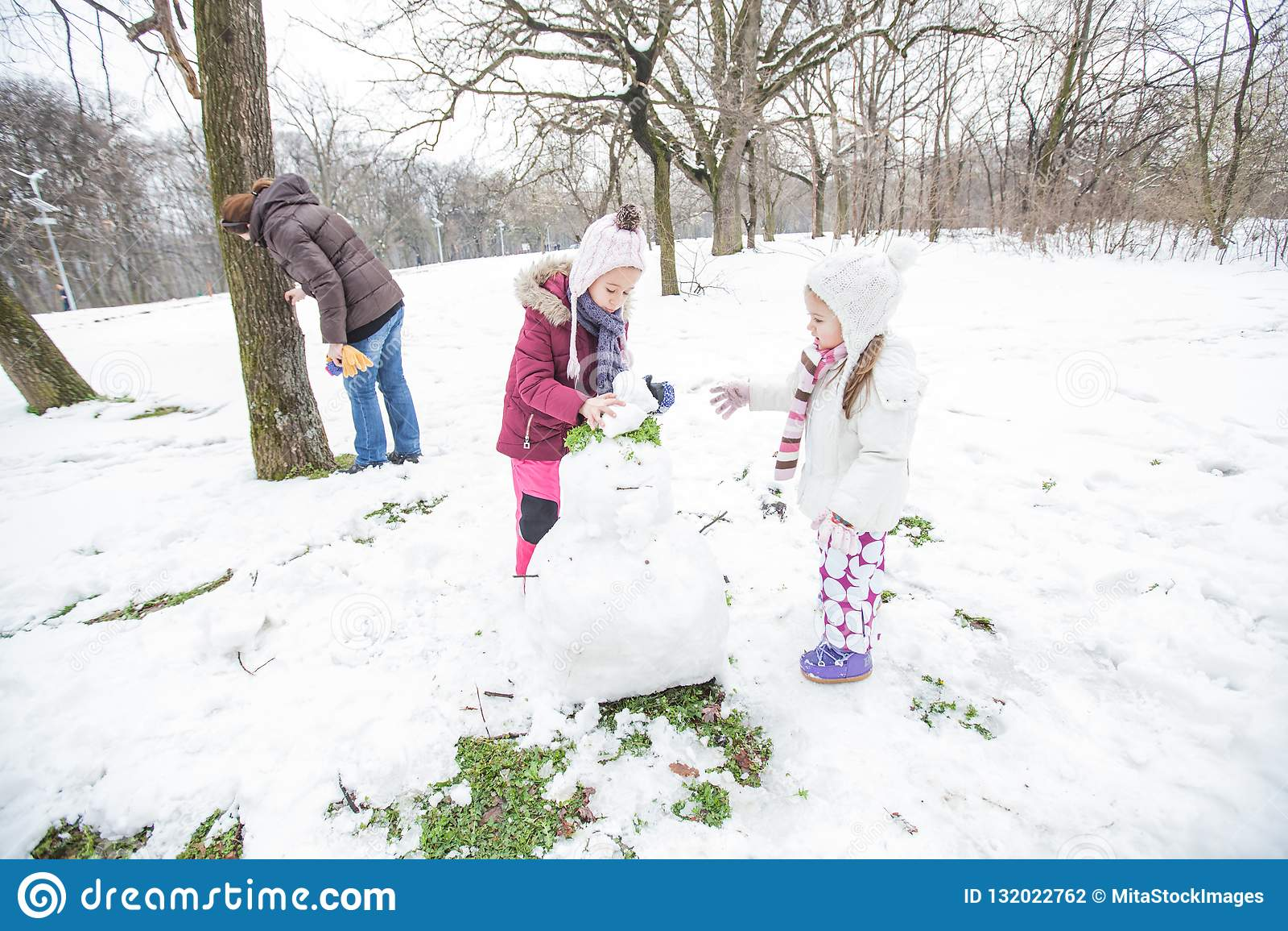Niño feliz que juega en nieve en el parque en el día de invierno