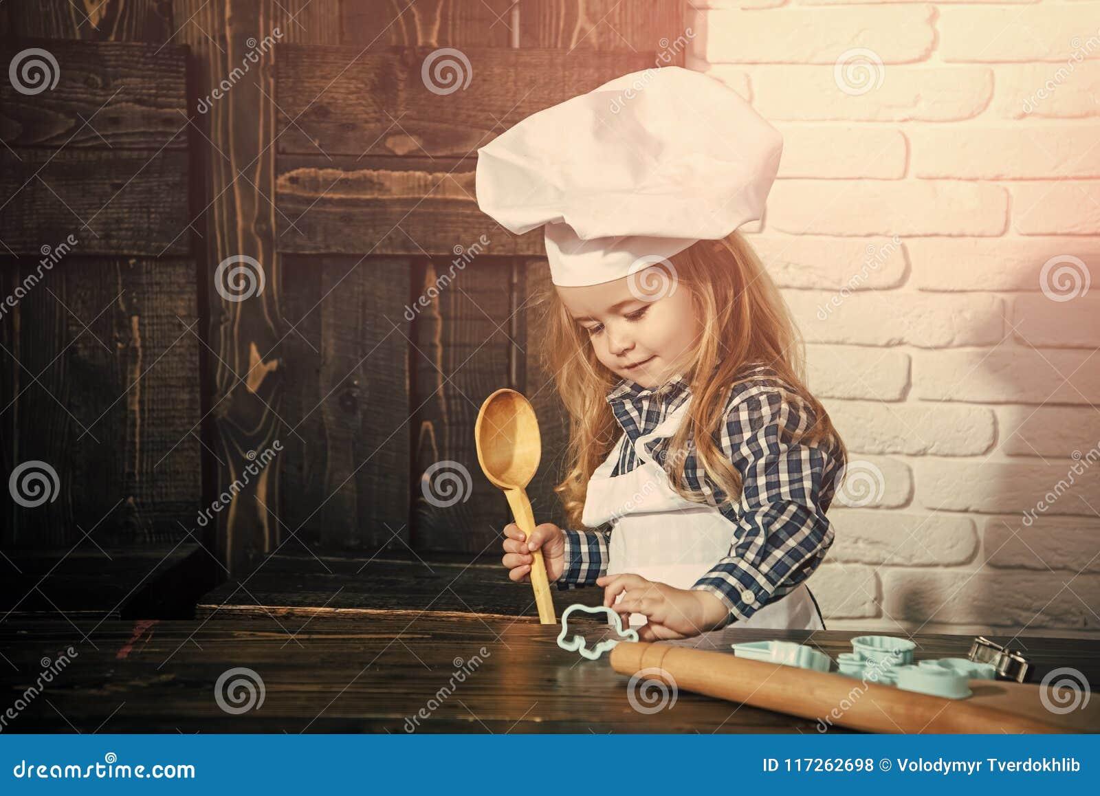 Niño feliz que se divierte Cocinero del muchacho en sombrero del cocinero y delantal en cocina
