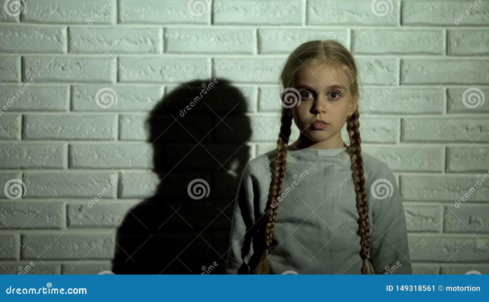 Ni?o femenino asustado que mira la c?mara, el concepto infantil de la fobia, del miedo y del horror