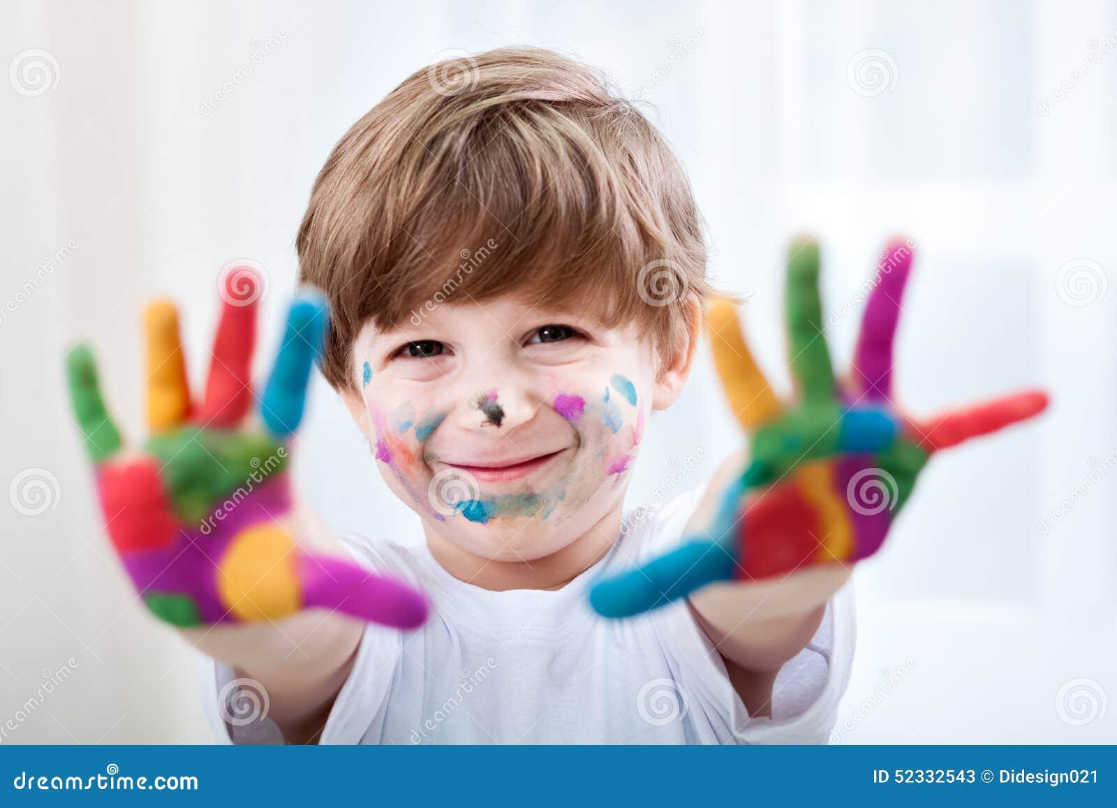 Niño hermoso sonriente que juega con colores