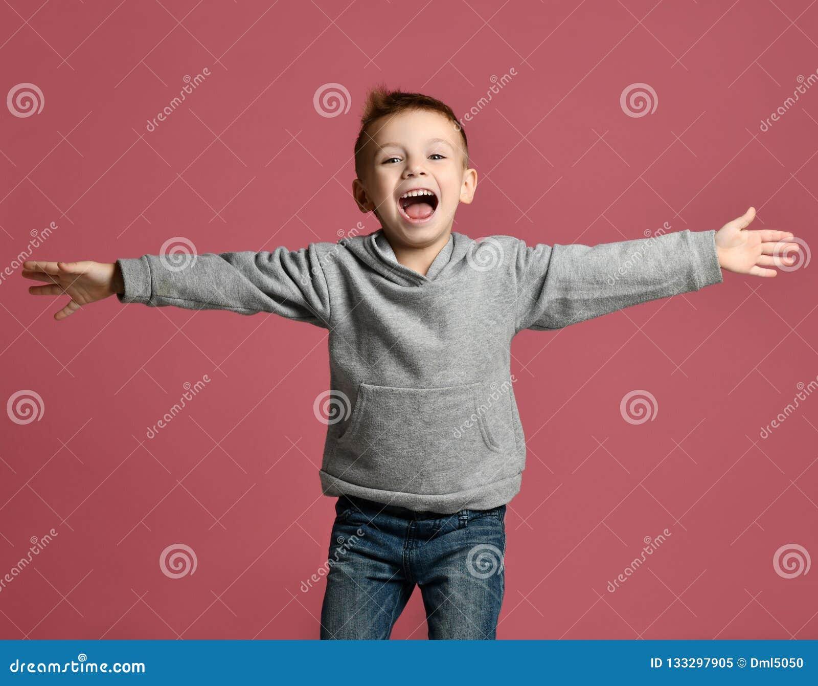 b6e64b83949 Niño joven del muchacho que salta en sudadera con capucha gris con las  manos separadas encima de la sonrisa de risa en fondo rosado
