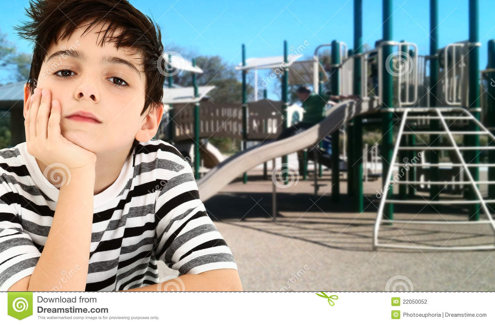 Niño joven hermoso del muchacho aburrido en el parque.