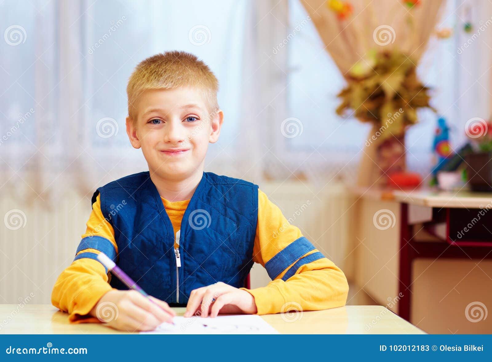 Niño lindo con la necesidad especial que se sienta en el escritorio en sala de clase