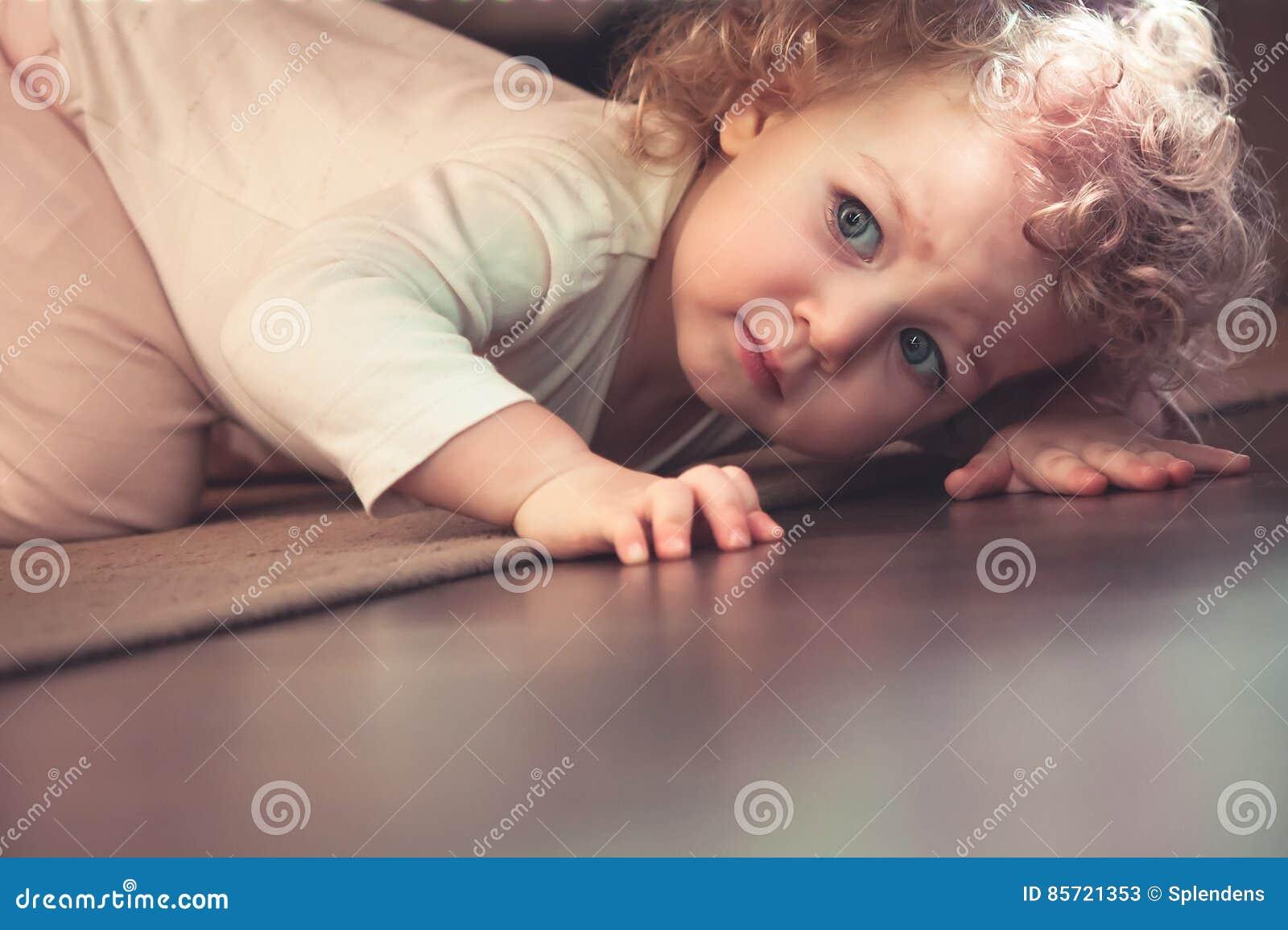 Niño lindo curioso que oculta debajo de la cama en sitio de los niños y que parece asustado