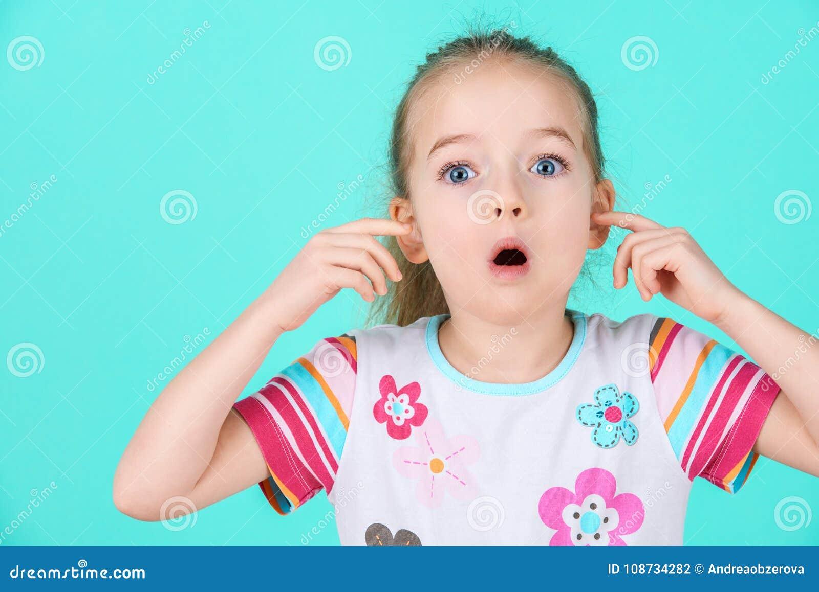 Niño obstinado con una actitud que ignora a los padres, bloqueando sus oídos con las manos
