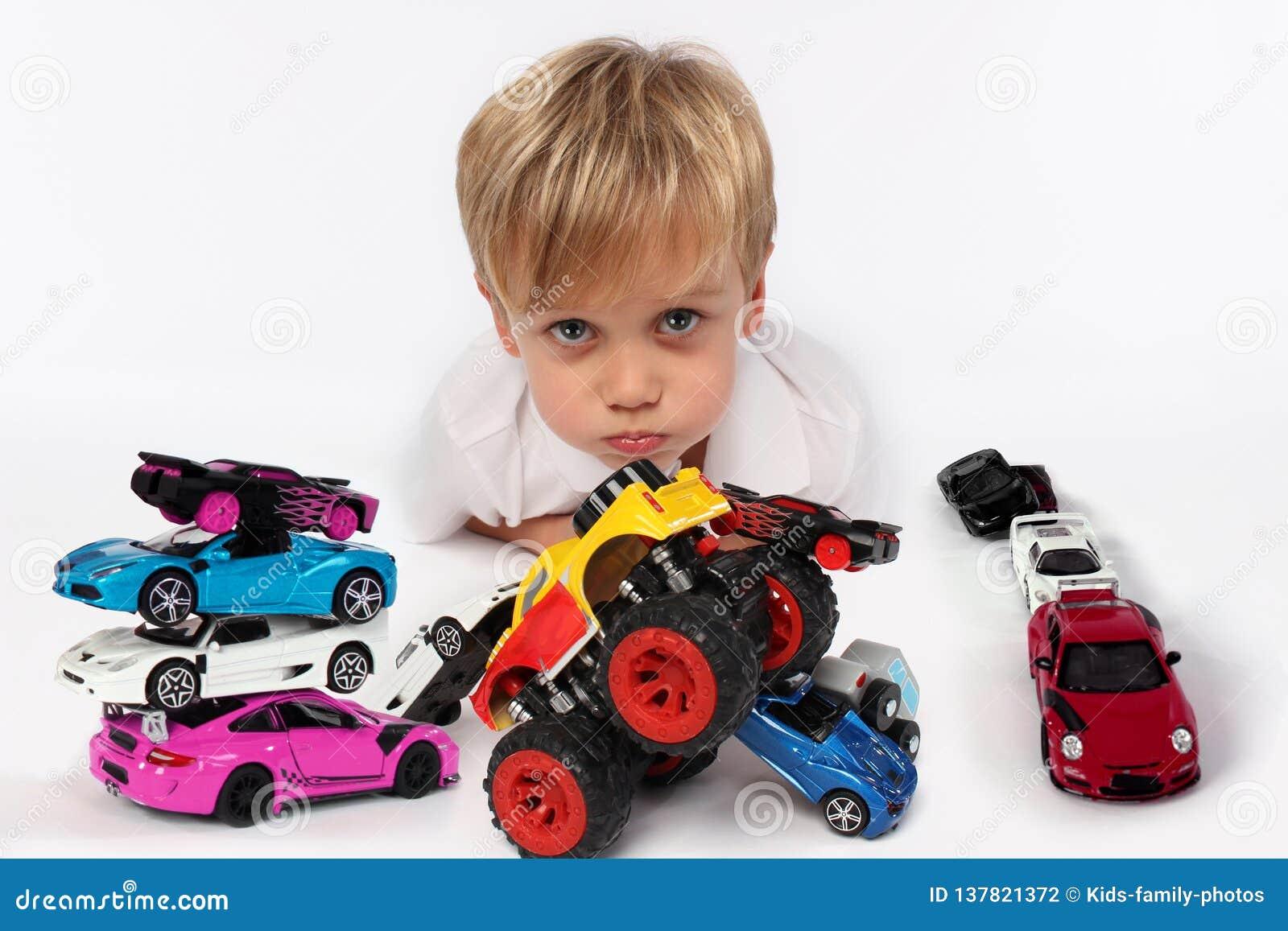 Niño pequeño adorable que miente rodeado todo por los juguetes del coche con sus mejillas y labios lindos listos para besar algui
