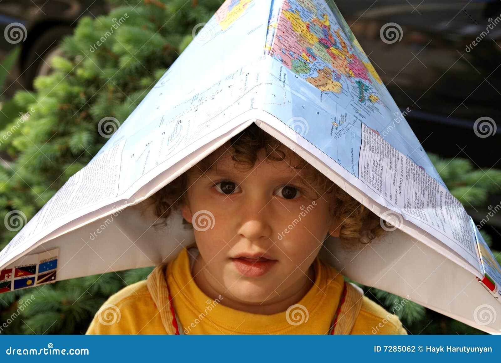 Niño pequeño bajo el casquillo de la correspondencia de mundo