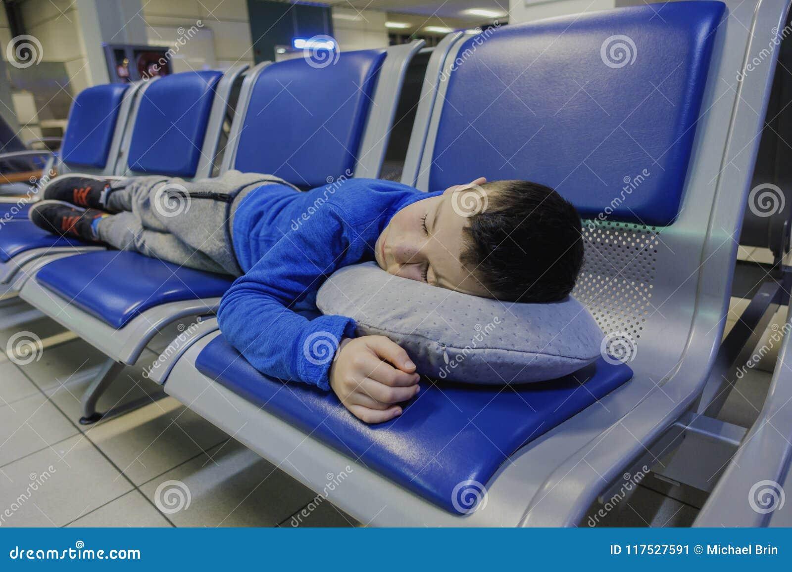 Niño pequeño cansado que duerme en silla mientras que espera vuelo en el aeropuerto