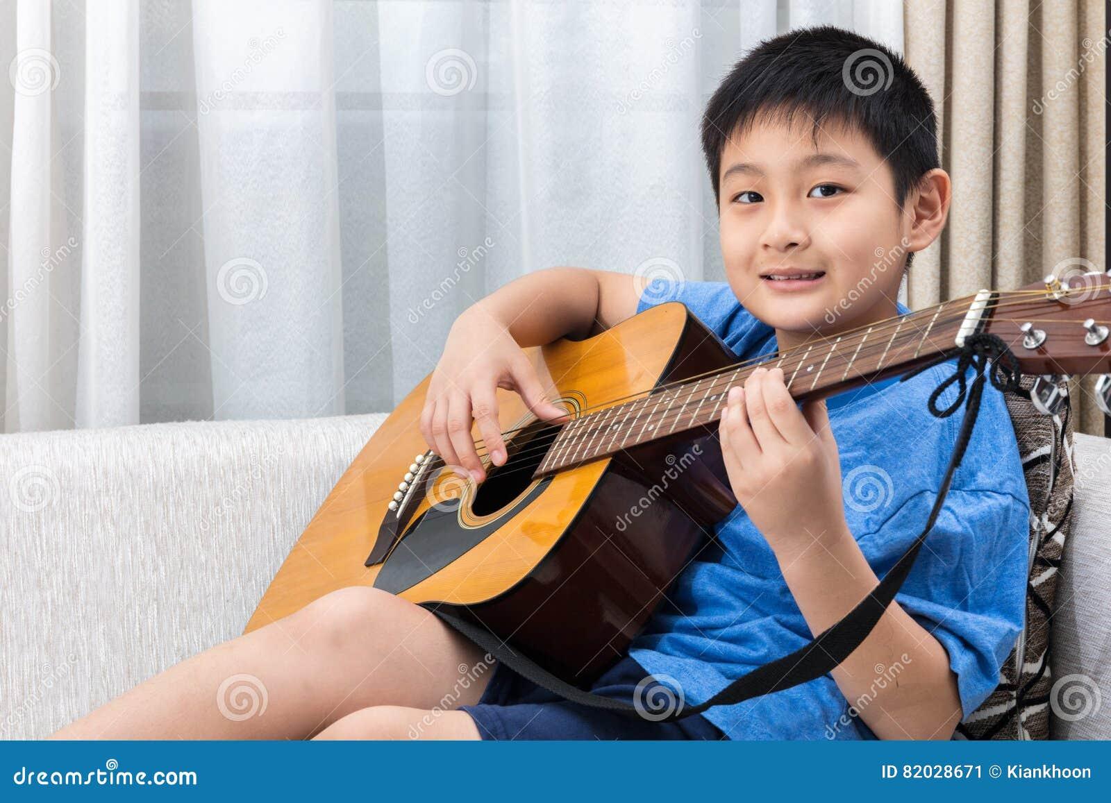Niño pequeño chino asiático feliz que toca la guitarra en el sofá
