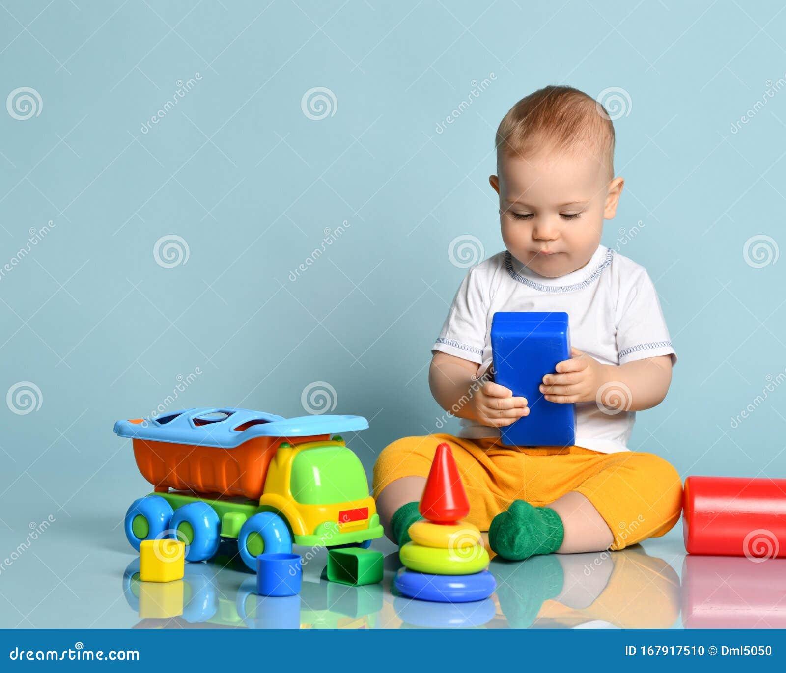 Nino Pequeno Con Pantalones Amarillos Y Camiseta Blanca Sentado En El Suelo Rodeado De Juguetes Coloridos Foto De Archivo Imagen De Pequeno Suelo 167917510
