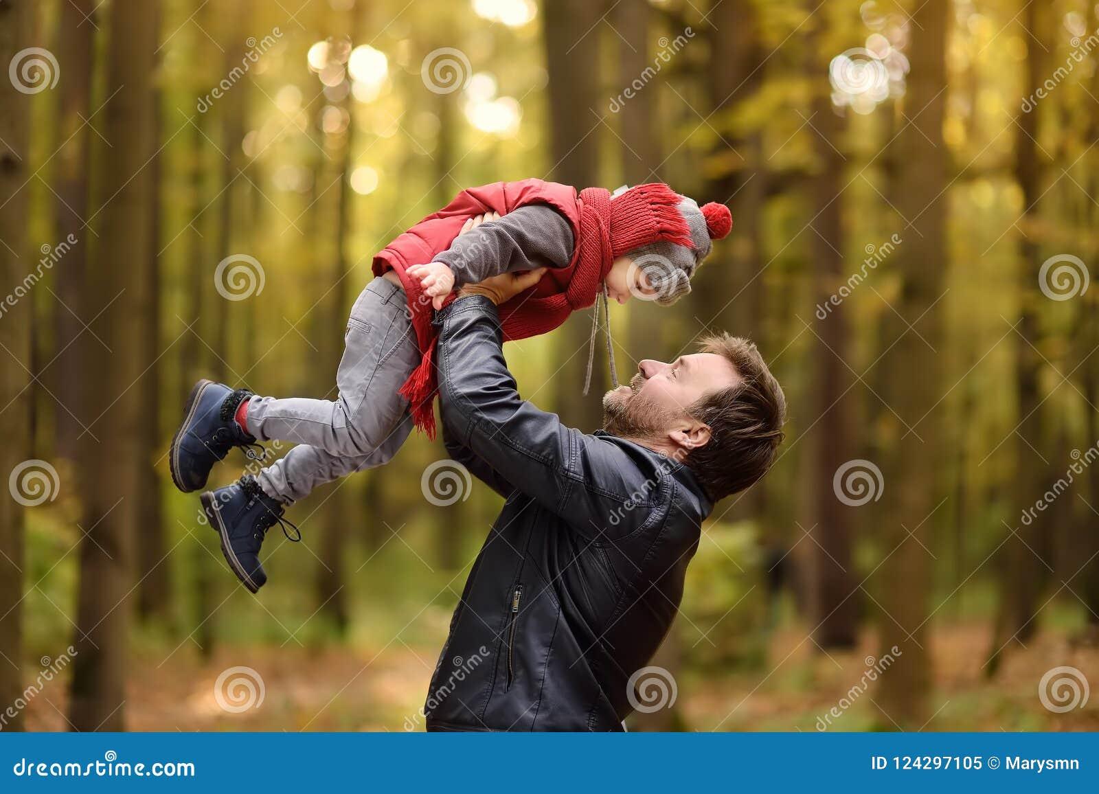 Niño pequeño con su padre durante paseo en el bosque