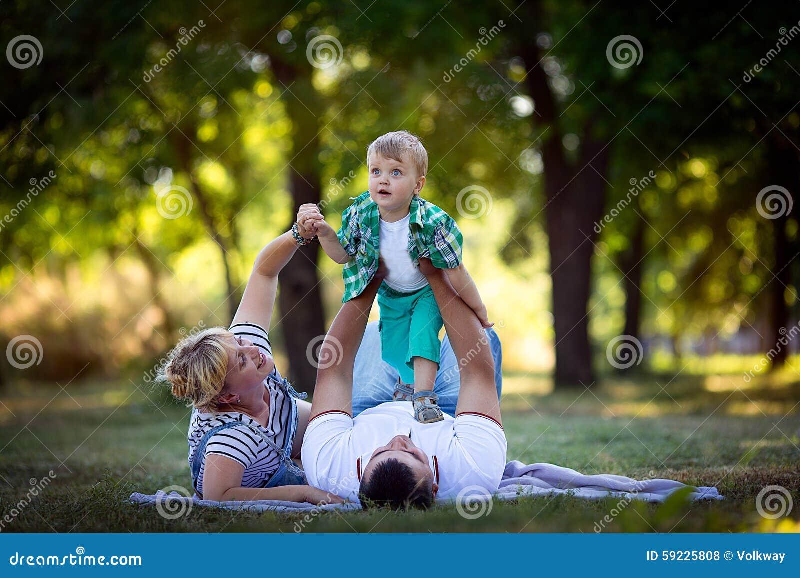 Niño pequeño con sus padres que se acuestan en la hierba