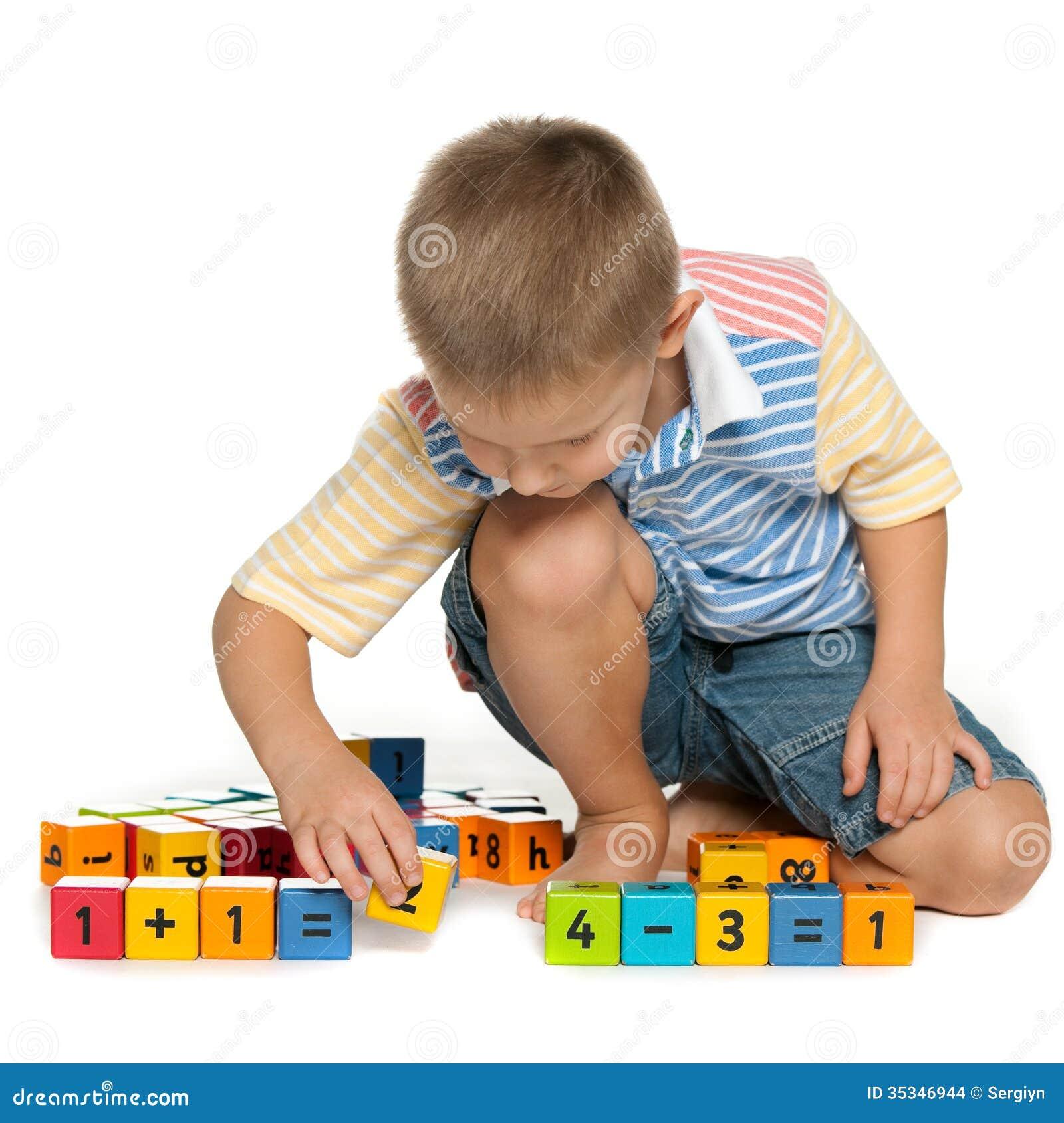 Ni o peque o concentrado con los bloques en el piso for Vivir en un piso pequeno con ninos