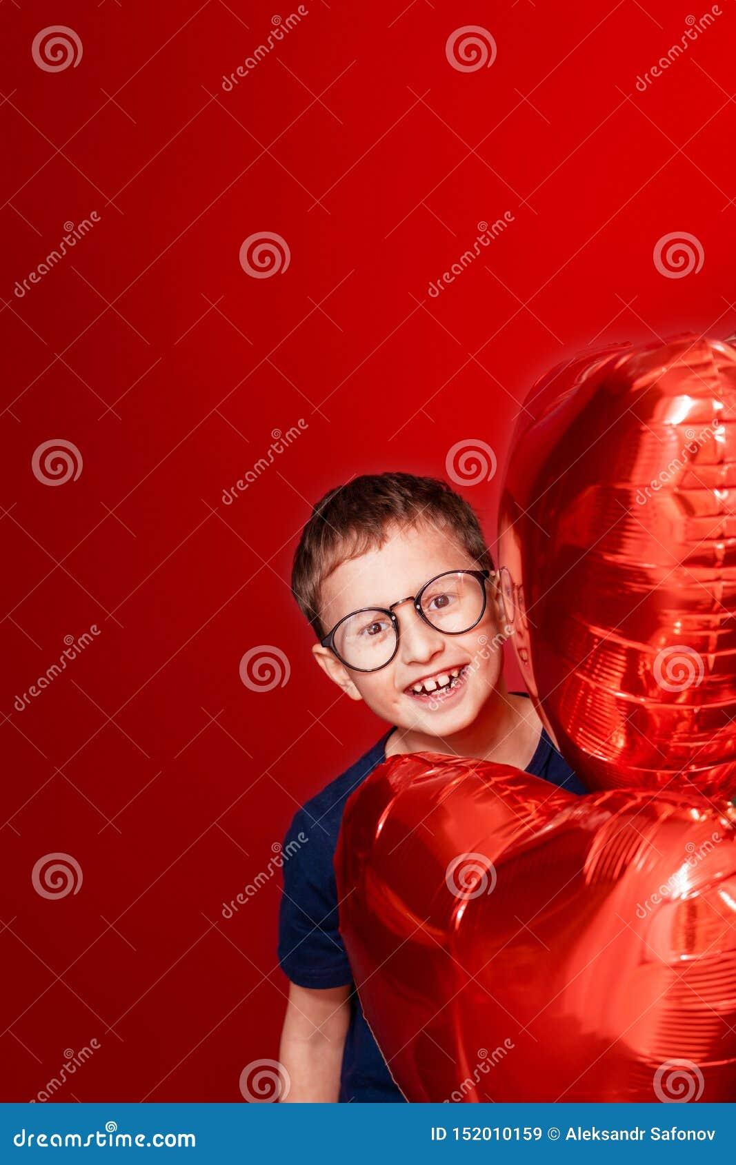 Niño pequeño de Laughting en vidrios, diverso corazón del color, los globos de la estrella para día de San Valentín o cumpleaños