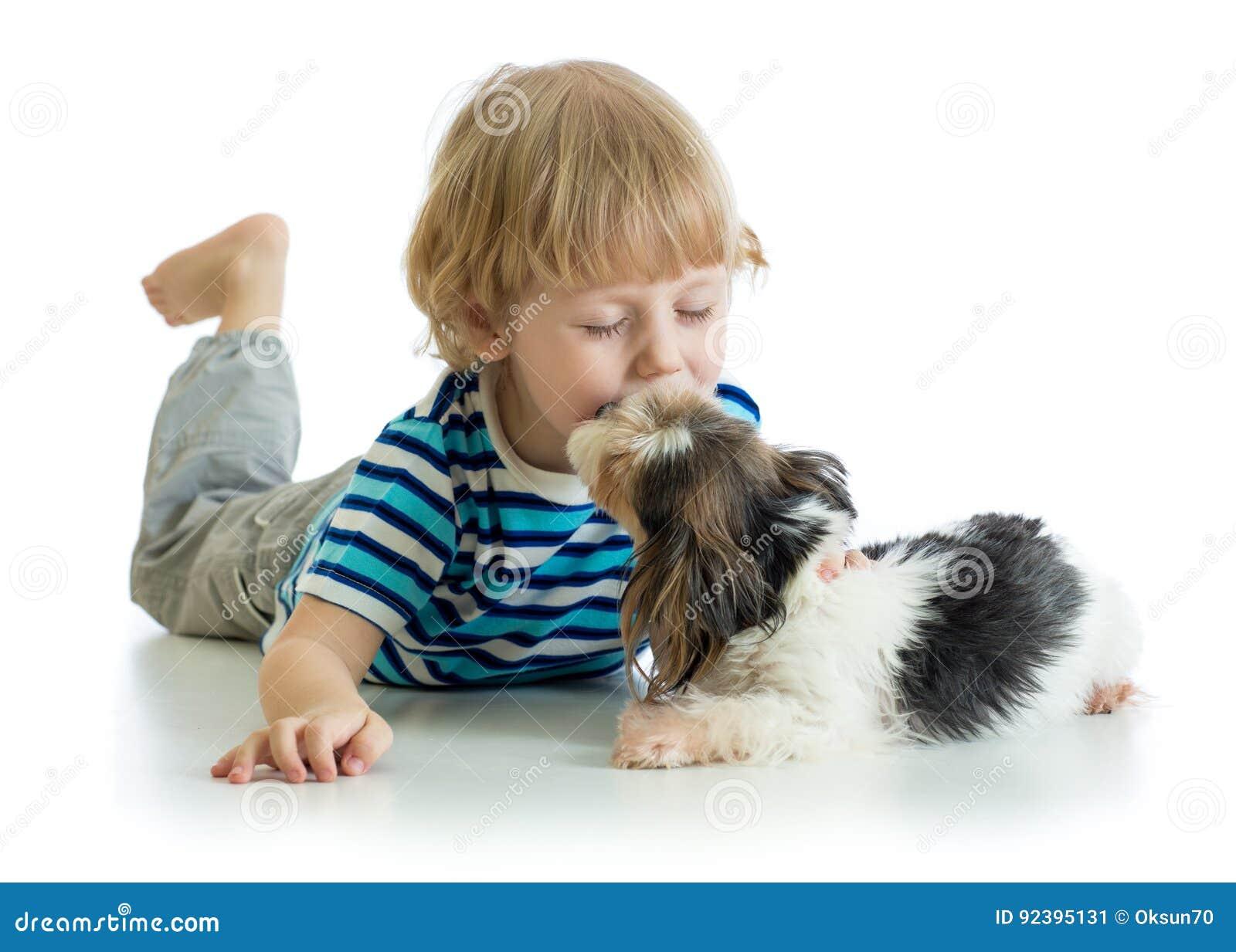 Niño pequeño del niño que besa el perro de perrito Aislado en el fondo blanco