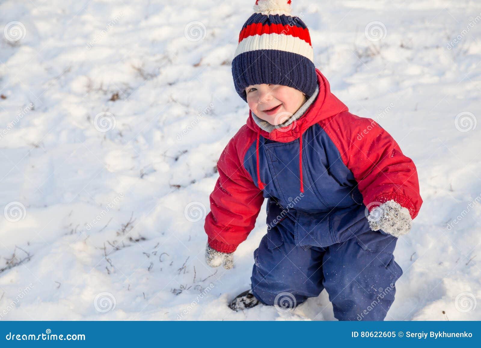 Niño pequeño divertido que camina en nieve