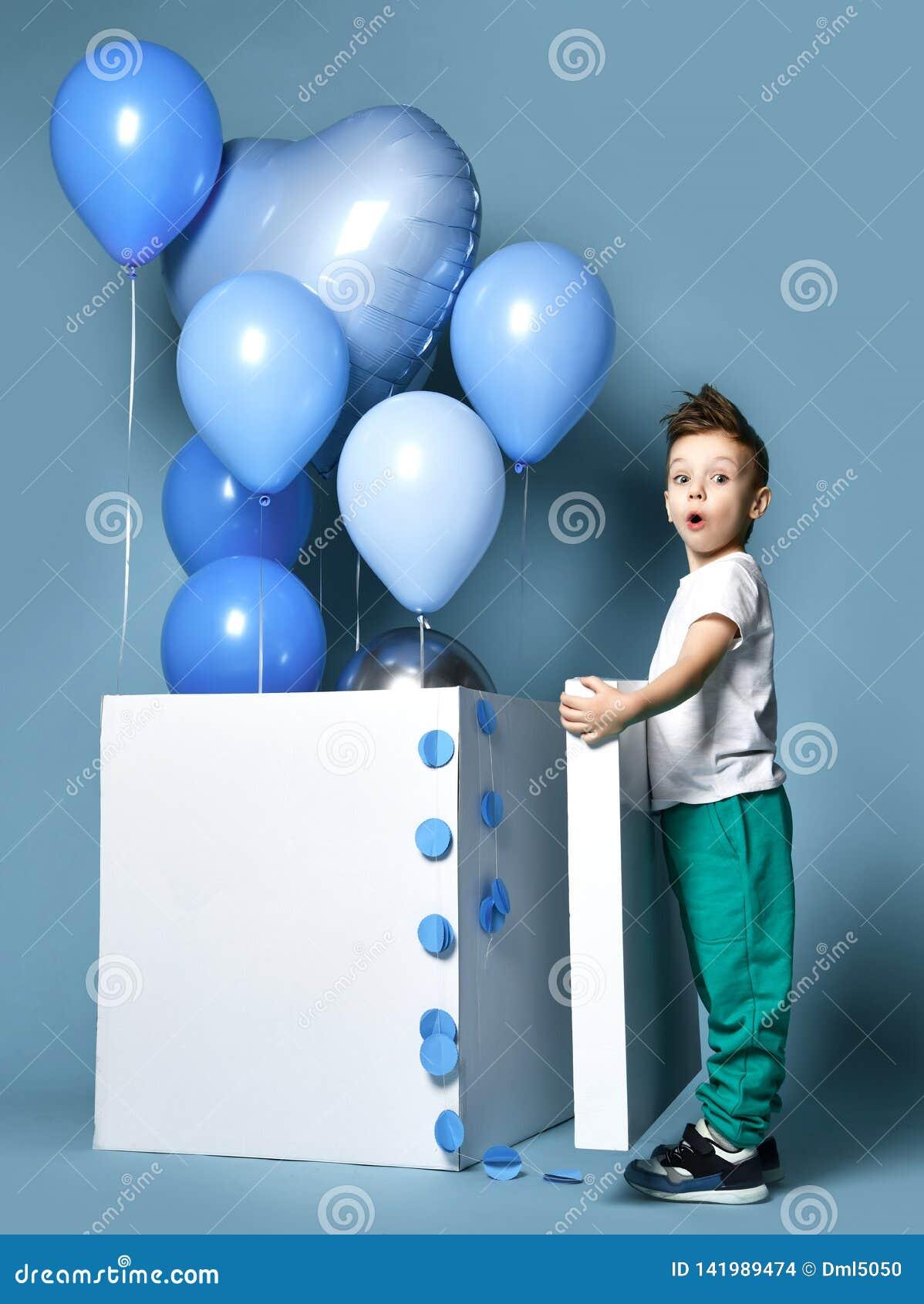 Niño pequeño feliz con los globos azules del color en colores pastel y la caja blanca vacía para la fiesta de cumpleaños
