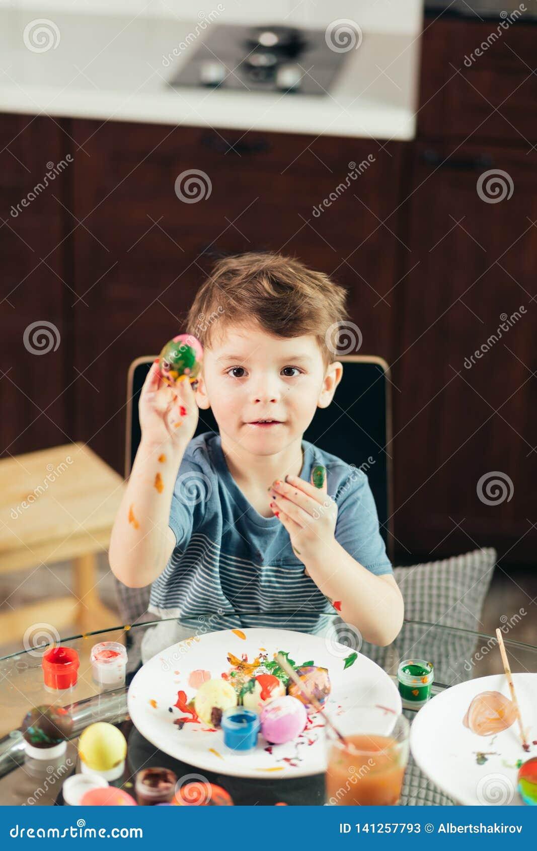 Niño pequeño feliz que pinta los huevos de Pascua, los niños y creatividad