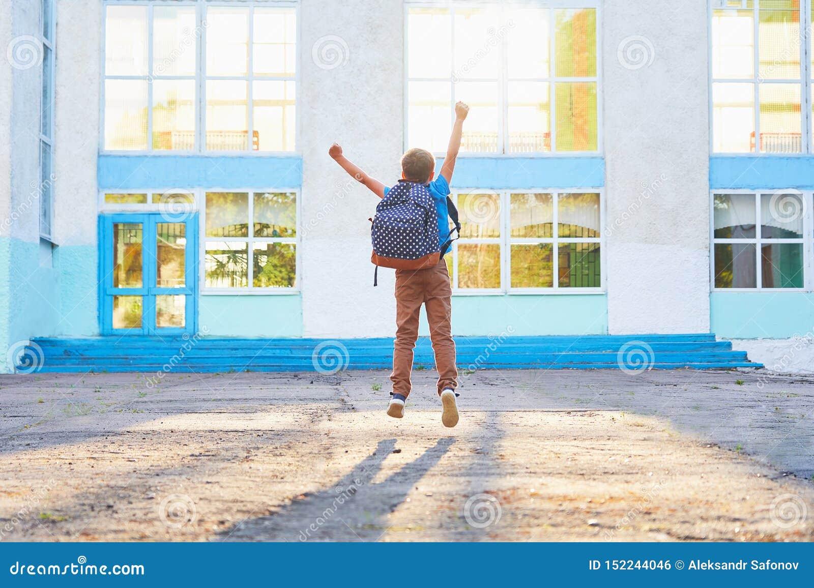 Niño pequeño feliz, salto de altura con alegría, el principio del año escolar el niño feliz va a la escuela primaria actitud posi