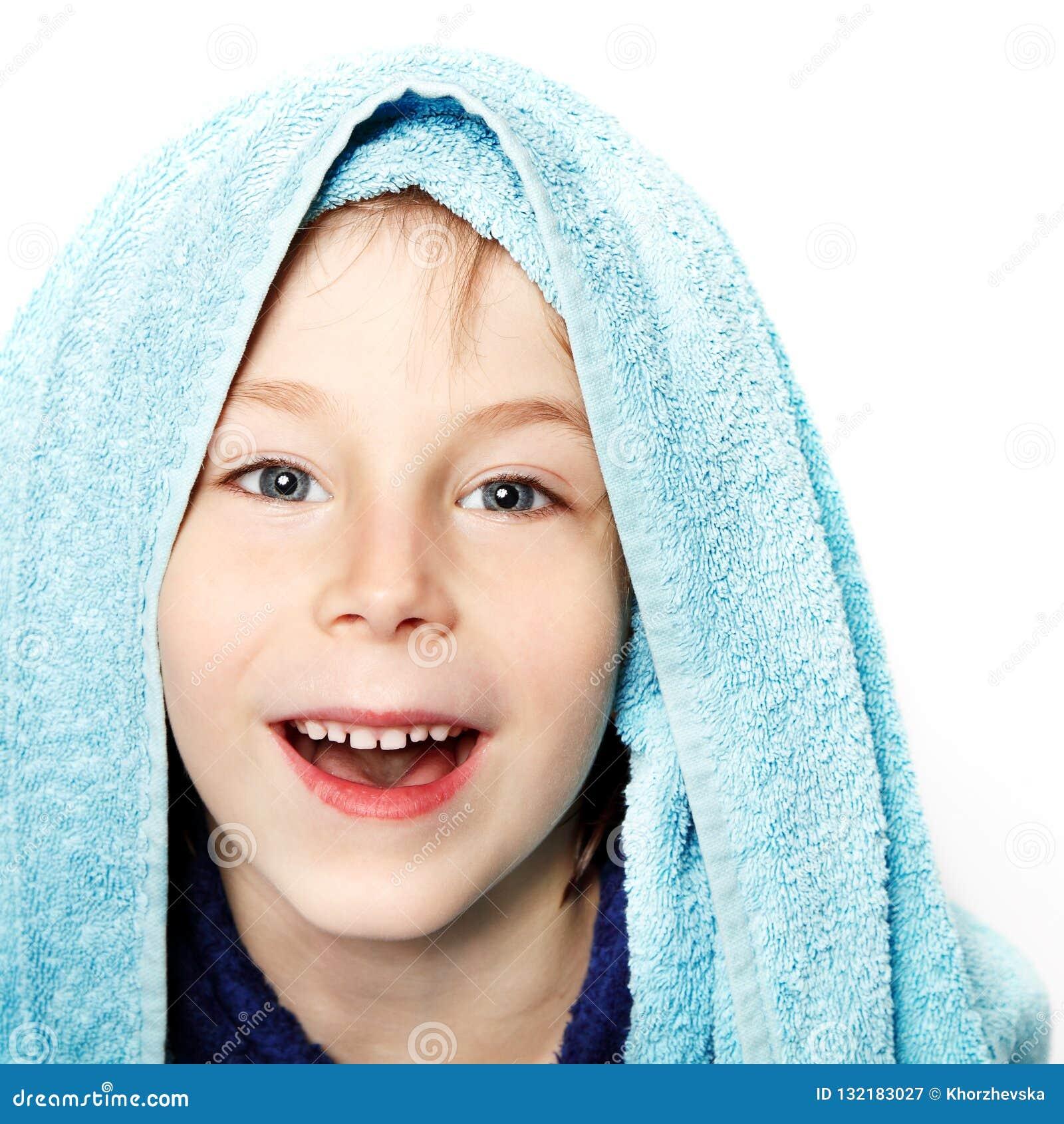 Niño pequeño hermoso después de ducha con la toalla de baño y el bathr azules
