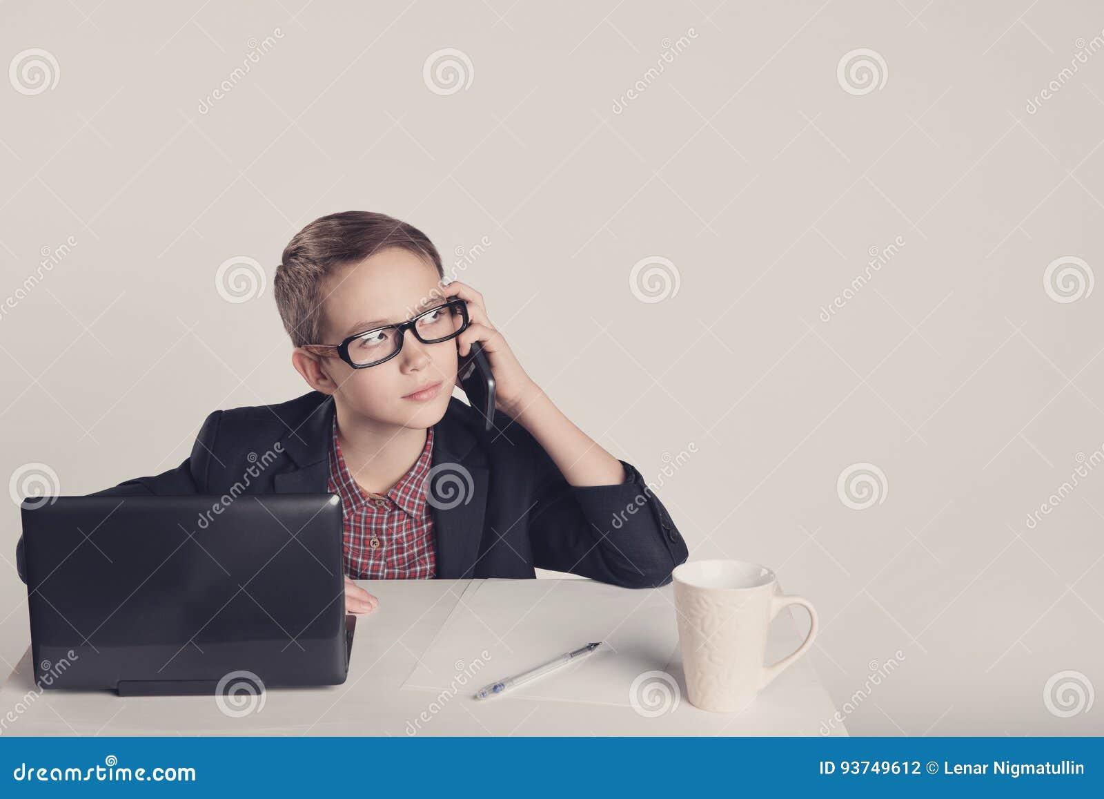 Niño pequeño lindo en un traje que habla en el teléfono