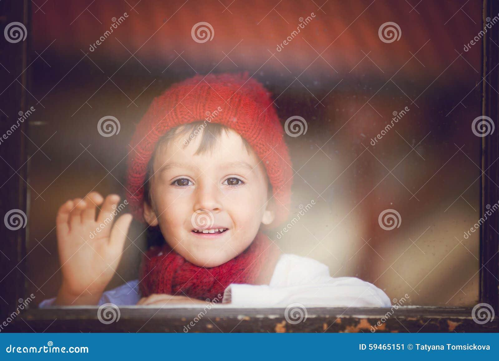 Niño pequeño, niño detrás de la ventana, sombrero que lleva y bufanda