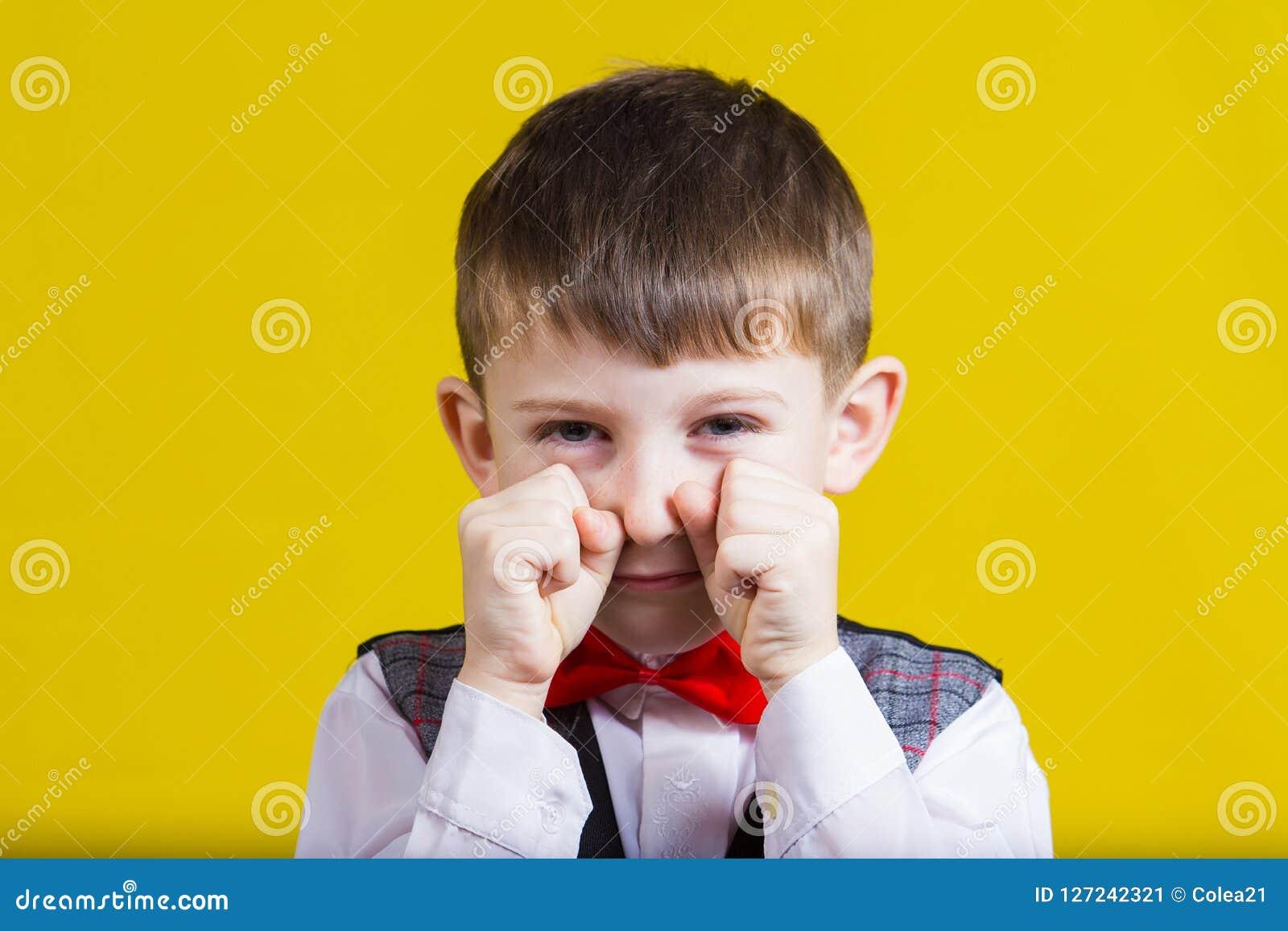 Niño pequeño obstinado, triste, trastornado, niño aislado sobre backg amarillo