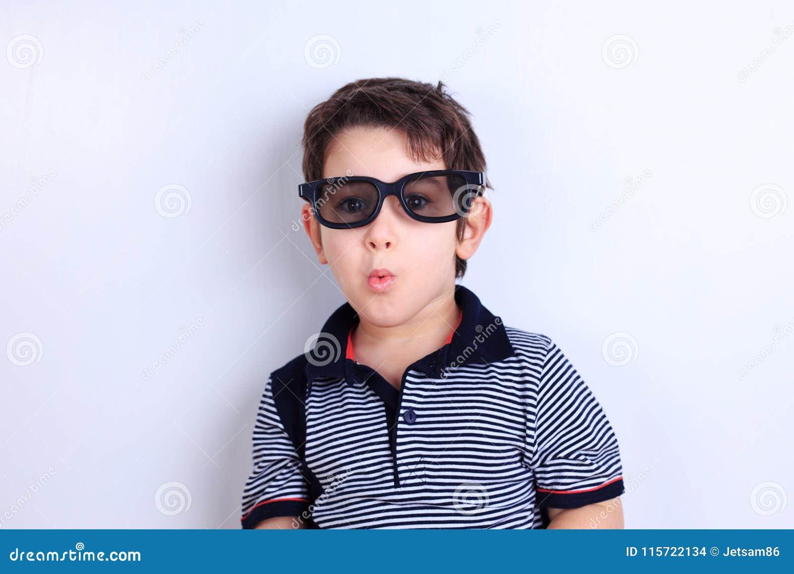 Niño pequeño precioso en las gafas de sol que soplan un beso, lanzamiento del estudio encendido