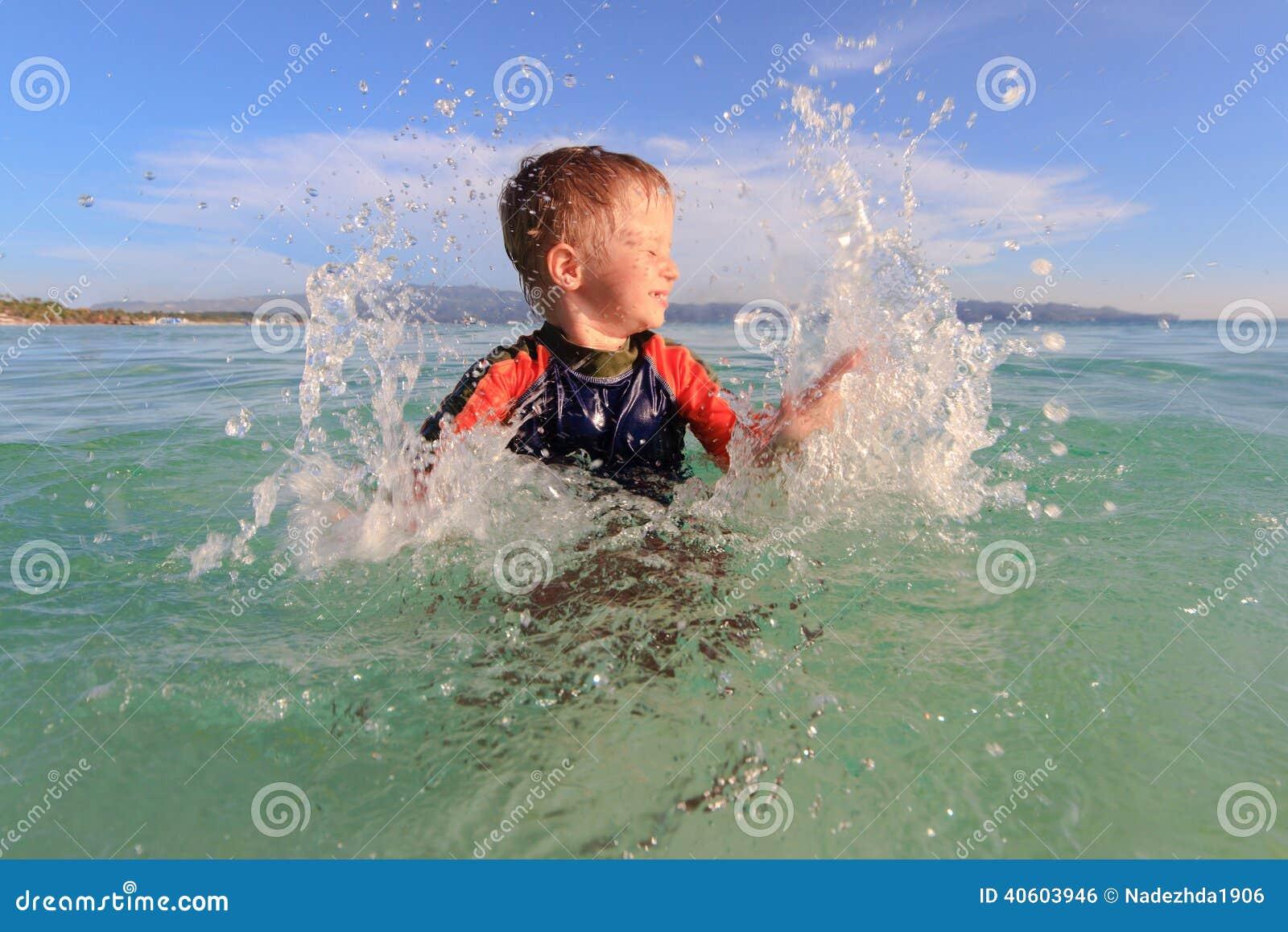 Niño pequeño que juega con agua en la playa
