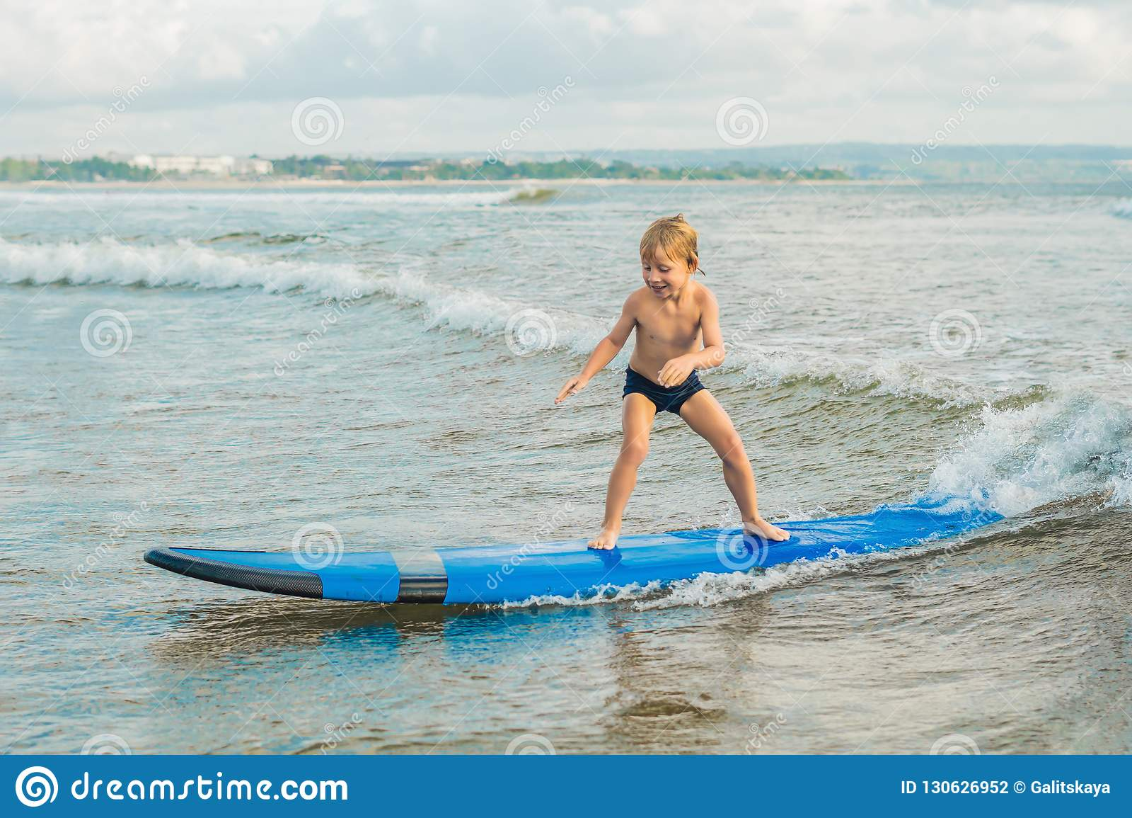 Niño pequeño que practica surf en la playa tropical Niño en el tablero de resaca en ola oceánica Deportes acuáticos activos para