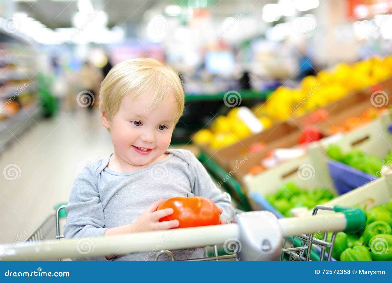 Ni o peque o que se sienta en el carro de la compra en un - Foto nino pequeno ...