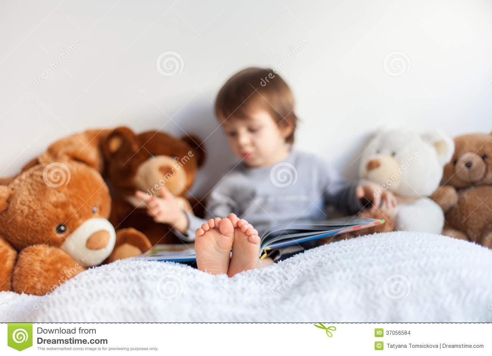 Ni o peque o sent ndose en la cama leyendo un libro foto - Foto nino pequeno ...