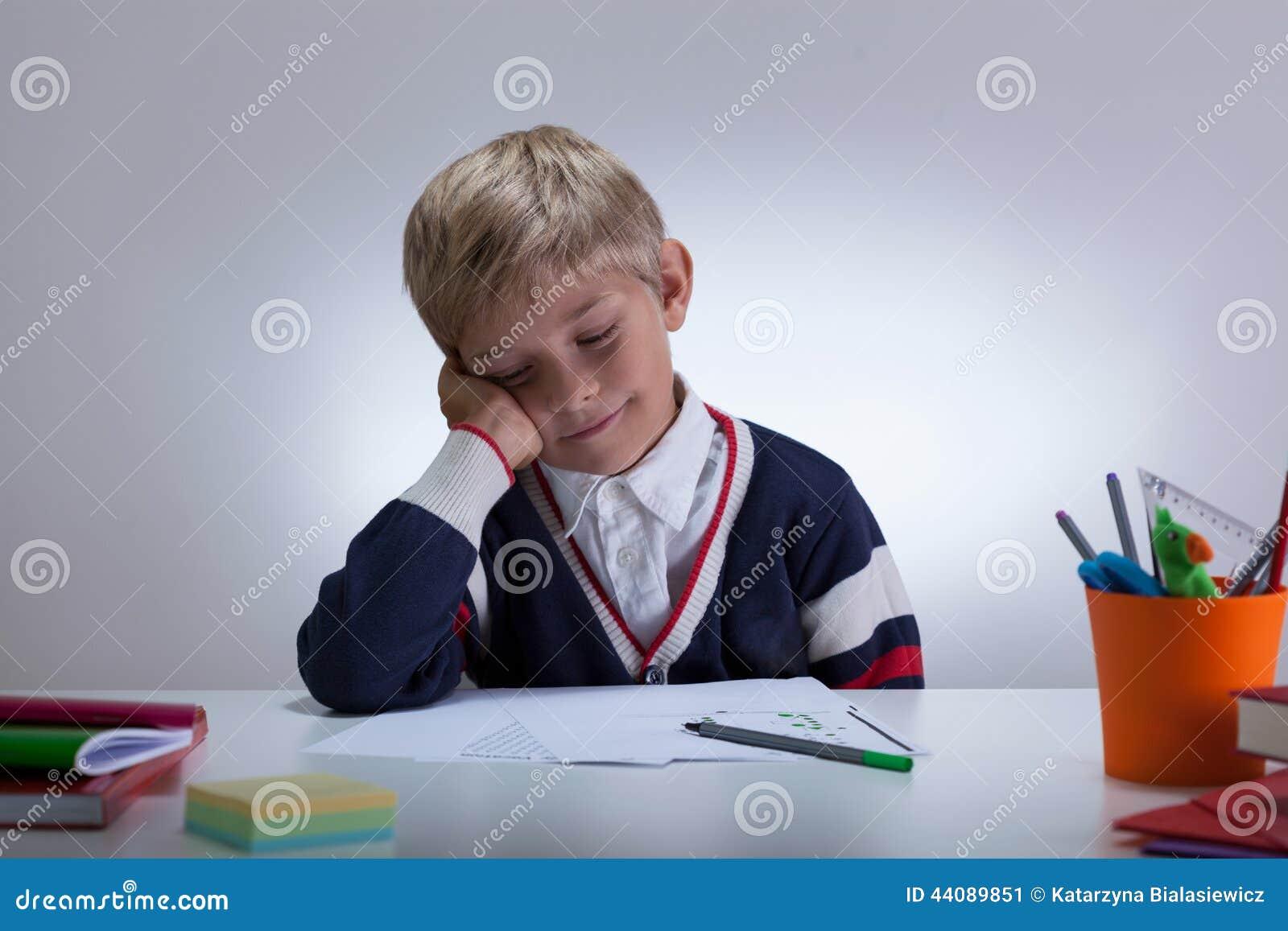 Niño pequeño soñoliento al lado del escritorio
