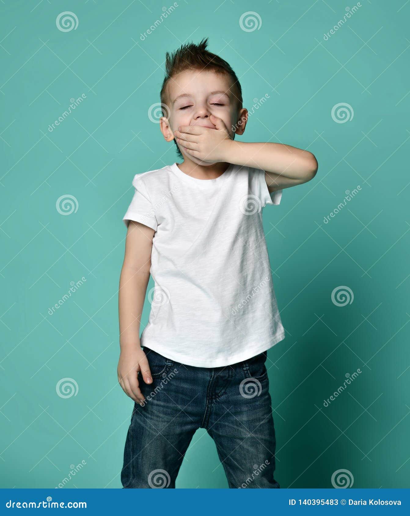 Niño pequeño soñoliento que bosteza y que mira la cámara