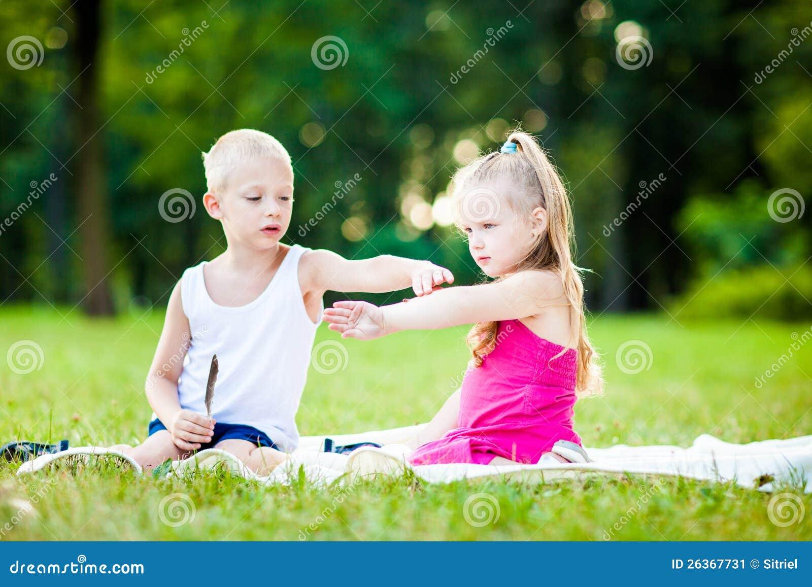 Niño pequeño y muchacha con la mariquita en parque
