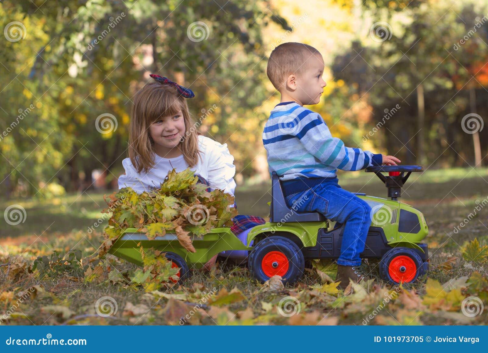 Niño pequeño y muchacha que juegan en el parque en un otoño hermoso DA