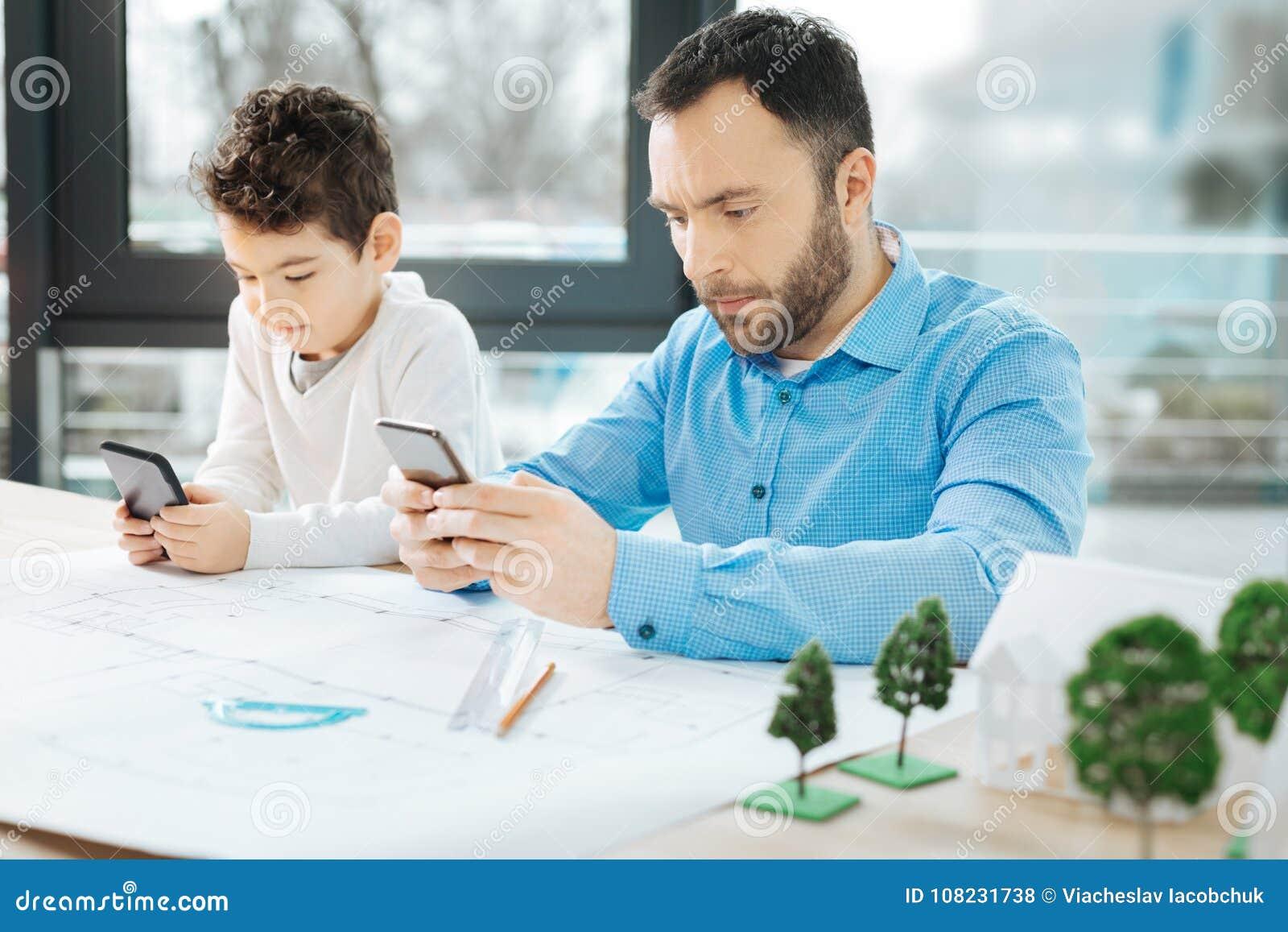 Niño pequeño y su padre que son pegados a sus teléfonos