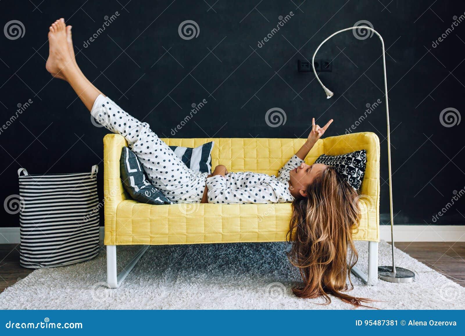 Niño pre adolescente en el sofá contra la pared negra en la vida moderna