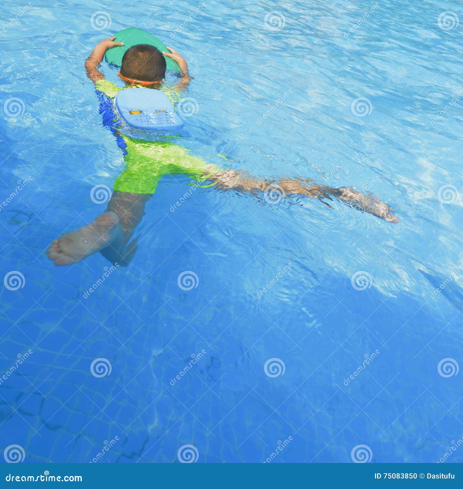 Niño que aprende nadar en verano